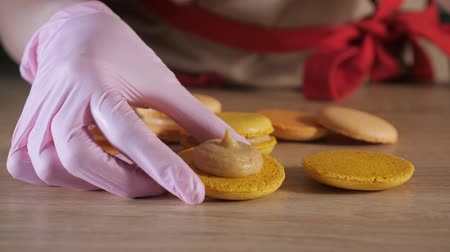pekař : Pastry chef is filling cream lemon macaroons with pastry bag, close-up. Dostupné videozáznamy