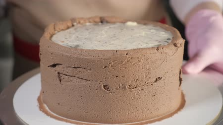 tutmak : Pastry chef woman is smearing chocolate cream on sponge cake with metal spatula on rotating cake stand in bakery, close-up. side view