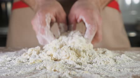 konfekció : Chef baker is kneading dough with flour by hands on the table, close-up.