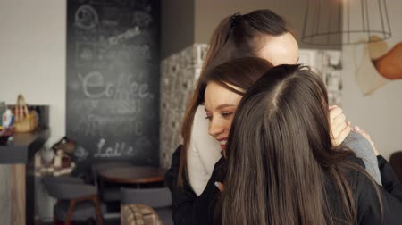 gentleness : Three women friends are hugging together greeting. Friendly meeting in cafe. Friendship concept.