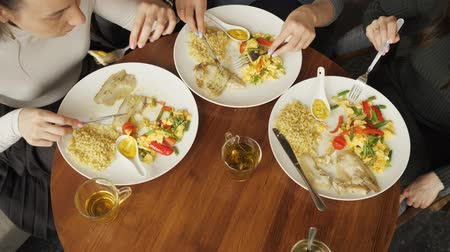 atender : Three women friends are eating their food in cafe. Plates on the table top view. Hands close-up.