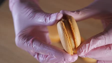 миндальное печенье : Pastry chef is filling cream lemon macaroons with pastry bag. Hands in gloves close-up. view from above Стоковые видеозаписи