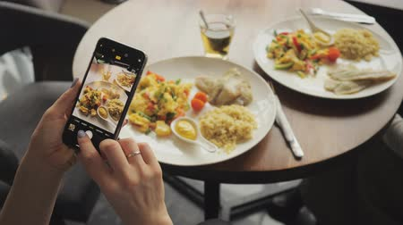 garfos : Woman blogger takes photos of her food in a cafe using mobile phone. Hands with phone screen close-up. Vídeos