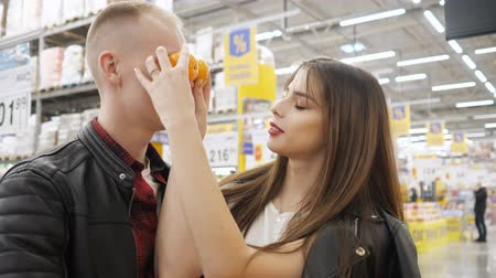 mandarinka : Young funny couple at the hypermarket. Girl is making grimace for boyfriend with tangerines in supermarket. Dostupné videozáznamy