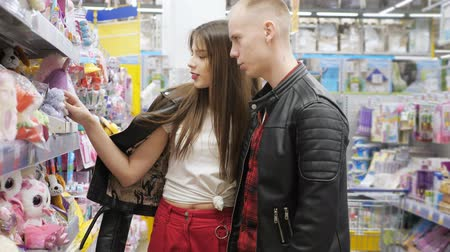 угождать : Young couple in supermarket is choosing soft toy for gift, close-up