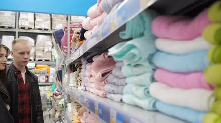решить : Young couple guy and girl are choosing towels at supermarket. Takeing towel in hand, considering and touching, side view. Стоковые видеозаписи