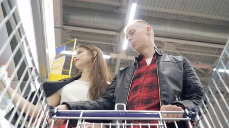 troli : Young couple guy and girl buy products in a supermarket and puts them in a trolley.
