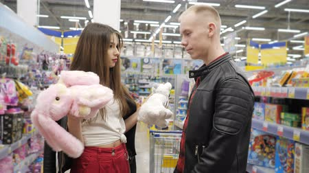 showcase : Young couple guy and girl in supermarket is choosing teddy toy - pink teddy hare or polar teddy bear. Stock Footage