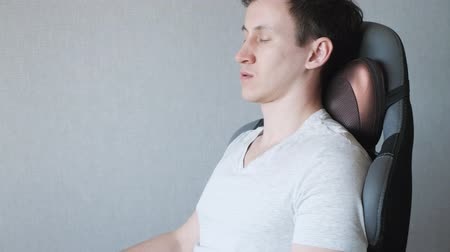 vibration : tired guy is sitting on the armchair with electric massage pillow, close-up