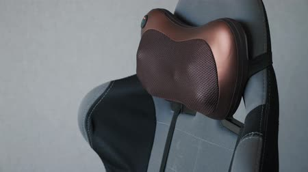 infrared : electric vibro massage pillow for neck on the armchair.