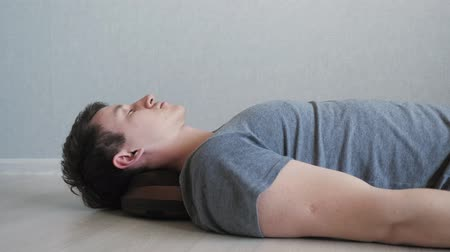 masażysta : tired guy is lying on the floor with electric massage pillow.