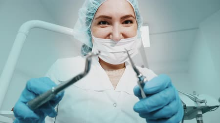 travessura : Portrait of dentist woman doctor in uniform is holding dental instruments forceps and needle in hands, toned. seen from patient pov