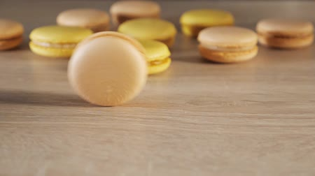işlenmiş : Yellow and beige macaroons on wood background, one cookie rolls across the table, front view