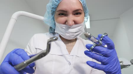 travessura : Portrait of dentist woman doctor in uniform is holding dental instruments forceps and needle in hands, patient point of view. Vídeos