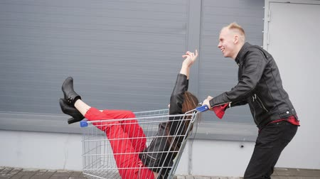 roll up : Guy rolls his attractive young girlfriend in the trolley on parking lot of the supermarket. Side view. Stock Footage
