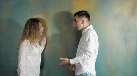 jealous : Young couple husband and wife are arguing and shouting each other standing near the wall, side view. Stock Footage
