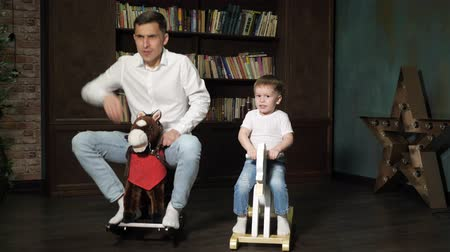 předstírat : Happy family young dad and little cute son are playing together riding on toy horses rocking chair in living room at home. Family time.