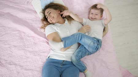 hozzábújva : Happy mom and son are having a fun family time together hugging laying in bed. Family lovely moments.