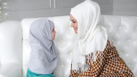 gentleness : Muslim family mom and daughter in hijabs and traditional clothes are sitting on the sofa at home, gently rubbing with noses and mom is kissing her daughters hands.