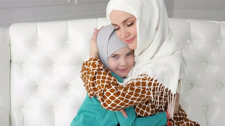 mother love : Muslim family mom and her little daughter in hijabs are hugging sitting on the sofa at home in modern white interior, side view.