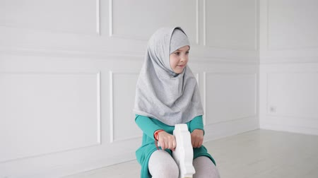 cavalos : Muslim teen 9 year girl in grey hijab and blue dress is playing riding on toy horse rocking chair in her white modern room.