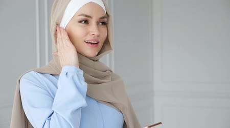 earpiece : Portrait of muslim young woman wearing beige hijab and blue dress is speaking mobile phone using wireless earpiece. Wireless hands free technology. Stock Footage