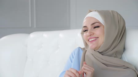 earpiece : Portrait of happy young muslim woman wearing beige hijab and blue traditional dress is dancing sitting on sofa and listening traditional music.