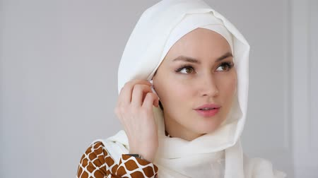 wearing earphones : Portrait of muslim young woman wearing beige hijab is putting wireless earpiece in her ear and speaking smartphone using headset. Wireless hands free technology.