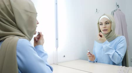 Muslim young attractive woman in beige hijab and traditional blue dress is applying lipgloss on her lips standing in front of the mirror.