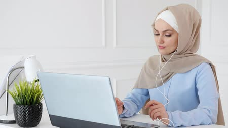 earpiece : Portrait of young muslim woman in hijab and traditional wear is listening music in earphones using laptop and enjoying it sitting at table. Stock Footage