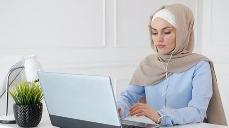 öğrenme : Portrait of young muslim woman in hijab and traditional clothes is learning english in earphones online using computer sitting at table.