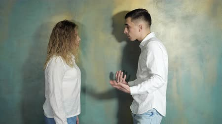 resent : Young couple husband and wife are arguing and shouting each other standing near the wall, side view. Stock Footage