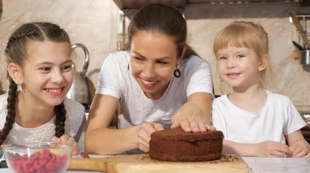 pekař : Family portrait of mom and daughters are preparing birthday cake together, mom is cutting sponge cake using knife in kitchen. Dostupné videozáznamy