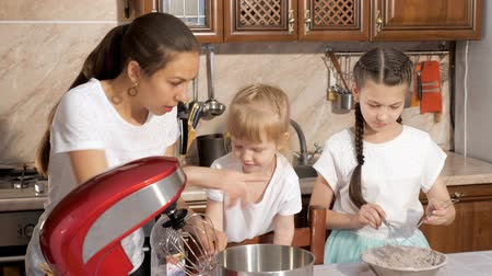magyarázza : Family cooking, mom pours some water into measuring cup, younger daughter wants to help her and holding out her hand. Woman explains recipe for her little girls. Stock mozgókép