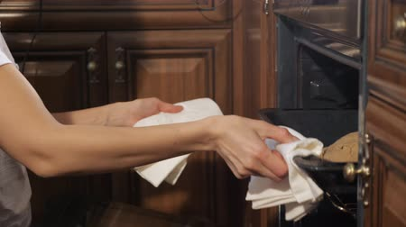 get out : Woman with kitchen towels in hands takes out of the hot oven a baking pan with cooked apfelstrudel in kitchen at home, hands closeup.