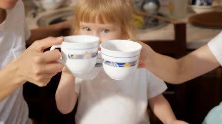 teacup : Portrait of little girl clinks tea cups with her family and drinks tea smiling sitting in the kitchen at home. Stock Footage