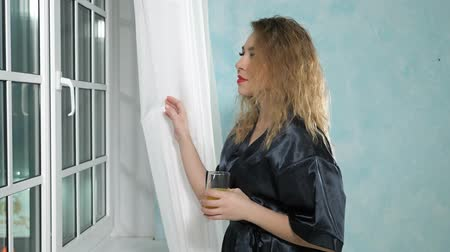 housecoat : Portrait of young beautiful curly-haired woman in black housecoat looks out the window in the evening smiling and drinking juice.