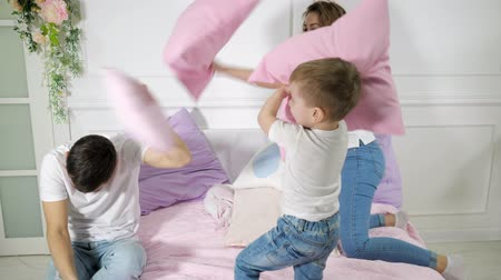 almofadas : Happy young family mom dad and little son are having fun pillow fight on bed, they are smiling, laughing and playing together in bedroom.