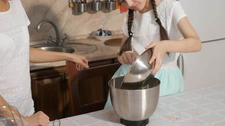 ón : Mother and teen daughter are cooking a sponge cake together in the kitchen at home, woman is holding a bowl to pour dough into cake tin and girl is helping her using a culnary spatula. Stock mozgókép