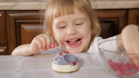 gąbka : Portrat of little cute girl is decorating small cake with raspberry in kitchen table at home and she is eating berries.