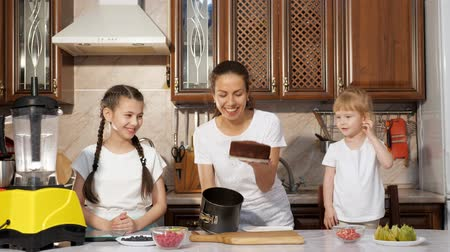 ón : Young brunette mother is baking birthday cake with her two little daughters in the kitchen, she is pulling the cake sponge out of the cake mold. Family cooking.