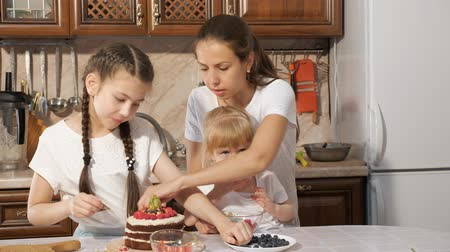 jagoda : Family cooking at home with children, portrait of mom with two daughters are decorating birthday chocolate cream cake with different berries together in kitchen at home. Wideo