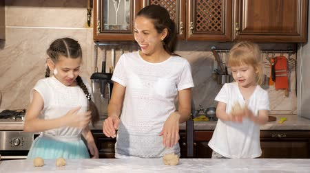 pekař : Portrait of playful mother and daughters are cooking dough for pie together in the kitchen and smearing each other in flour, touching noses with dirty hands, funny time together.