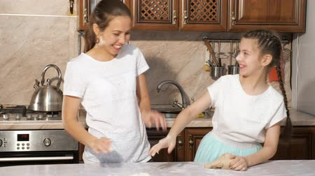 mischief : Portrait of playful mother and teen girl daughter is cooking dough for pie together in the kitchen and smearing each other in flour, touching noses with dirty hands.