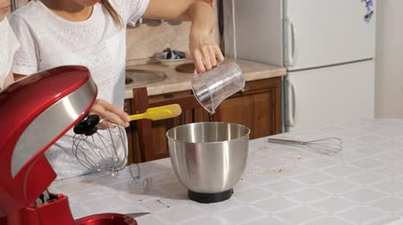 blúz : Unrecognizable woman in white blouse is pouring syrup in mixer bowl from measuring cup using spatula to cook cream for cake in kitchen at home, closeup view.