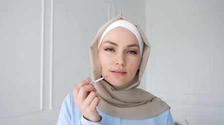 kompakt : Portrait of young muslim woman in beige hijab and traditional blue dress is applying compact powder with sponge on her face looking at small mirror at home, side view.