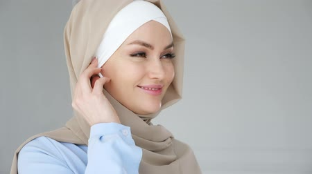 earpiece : Portrait of muslim young woman wearing beige hijab and blue dress is putting wireless earpiece in her ear and speaking smartphone using headset. Wireless hands free technology. Stock Footage