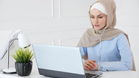 begrijpen : Portrait of young muslim woman in hijab and traditional clothes is learning english in earphones online using computer sitting at table.