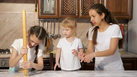 pekař : Two daughters is helping their mom to cook dough for pie, mother explans how to knead the door.