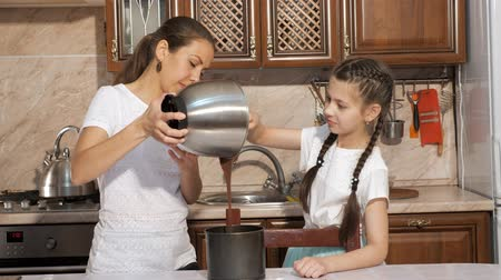 lata : Mother and teen daughter are cooking a sponge cake together in the kitchen at home, woman is holding a bowl to pour dough into cake tin and girl is helping her using a culnary spatula. Stock Footage